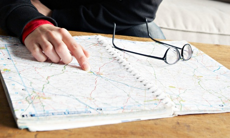 Woman looking up directions in a roadmap